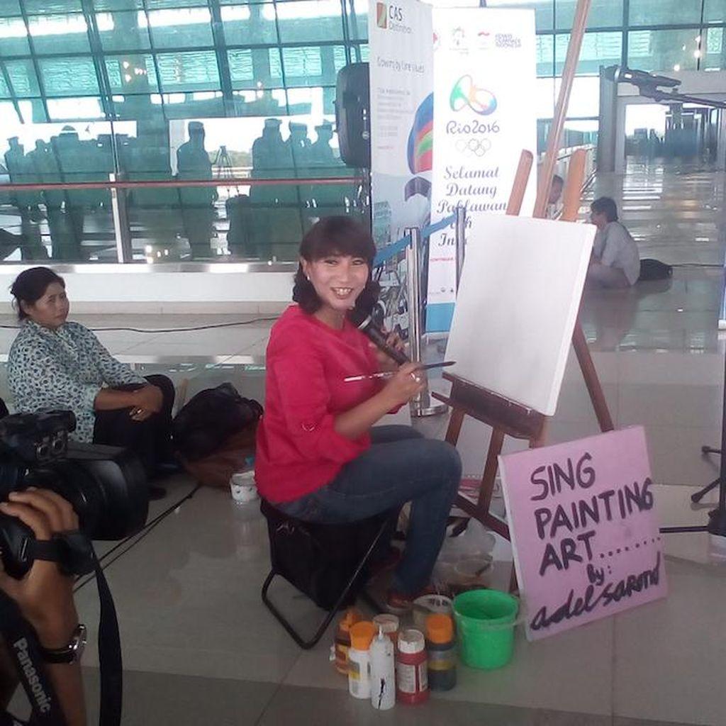 Tunggu Sang Pahlawan di Bandara, Wanita Ini Melukis Owi/Butet dan Menyanyi