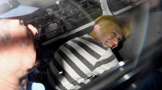 Uematsu tersenyum saat dibawa ke Jaksa untuk diperiksa