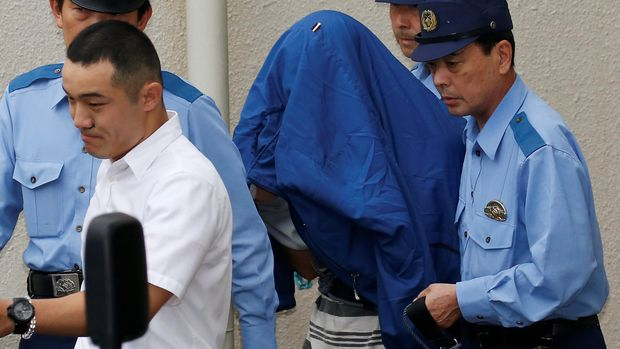 Umatsu menutupi wajahnya saat dibawa oleh Polisi setempat