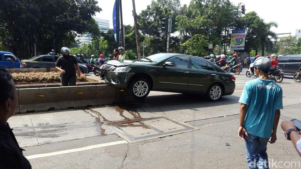 Bruuuk! Camry Hijau Ringsek Tabrak dan Nyangkut di Separator Busway