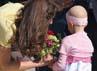 Kate menerima bunga dari seorang bocah penderita kangker saat tiba di bandara. Chris Jackson/Getty Images.