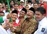 Ketua Umum PKB, Muhaimin Iskandar (kiri), Ketua Umum PBNU Said Aqil Siraj(tengah) dan Ketua PKB Andi Muarly Ramlie (kanan) memegang bendera merah putih dan NU  saat penutupan Kirab Resolusi Jihad.
