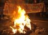 Sejumlah aktivis mahasiswa membentang spanduk di belakang ban yang dibakar untuk memblokade jalan di depan Kampus YAI, Salemba, Jakarta, Kamis (29/3) malam. ANTARA/Ismar Patrizki.