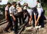 Petugas PT KA mengeruk batu yang menutupi rel di kawasan Palmerah, Jakarta.