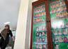 Seorang petugas Panti Sosial Asuhan Anak Balita Tunas Bangsa, melintas di samping bingkai besar foto para anak yang terlantar, yang mendapatkan penaganan dan perawatan.