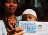 Warga menunjukkan kartu pemilih milik suaminya.