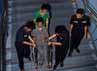 Petugas KA membantu penumpang penyandang cacat menuruni tangga.