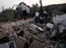 Warga mencari korban di puing-puing bangunan. AFP/Mehr News/Mahsa Jamali.
